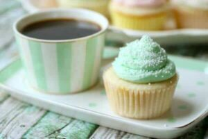 Pastel green frosted white cupcake on a pastel green plate with a cup of coffee nearby.