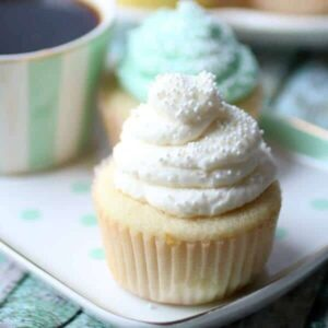 Recipe image for recipe card - white cupcake with a towering mass of whipped cream cheese frosting on top