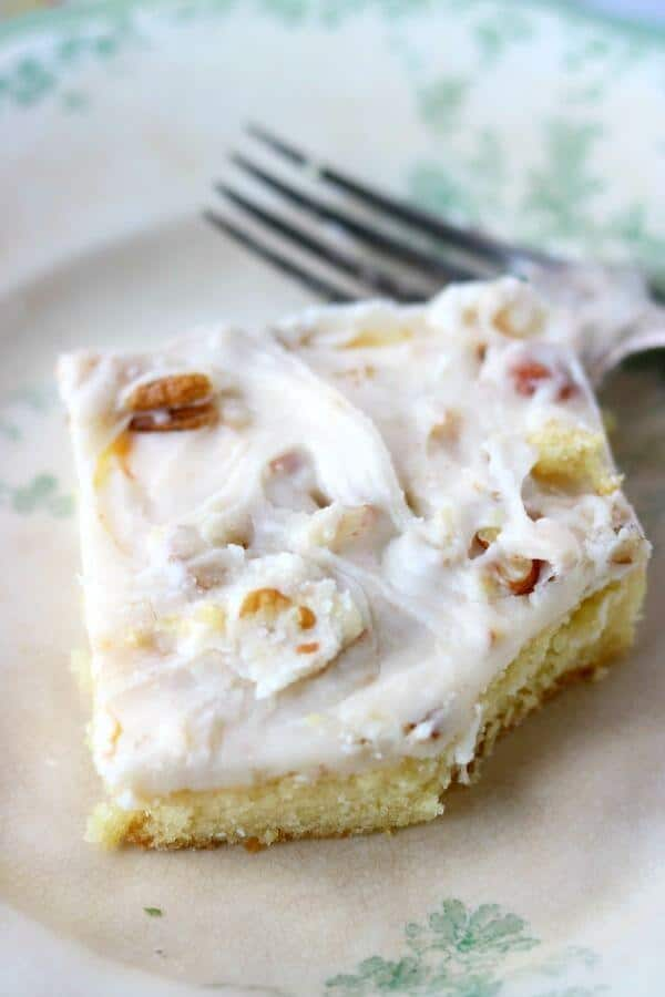 Gooey white icing and pecans on top of a sheet cake.
