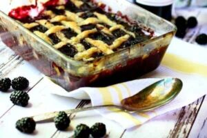 Feature image of a baking dish of blackberry cobbler on a white and yellow kitchen towel.