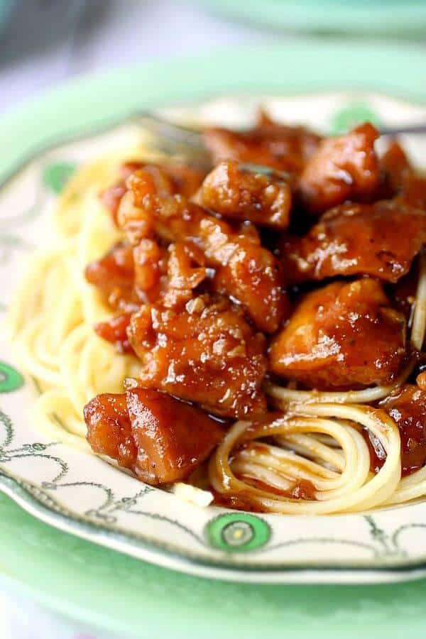 Closeup image of bourbon chicken covered with the sweet-tangy glaze on an antique china plate.