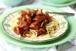 bourbon chicken with a bright, sticky glaze on a bed of pasta. Feature image
