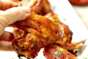 Spicy oven baked chicken wings are being picked up with fingers.