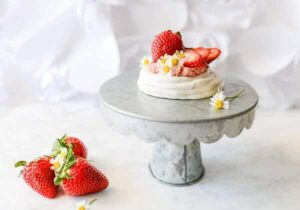 A small strawberry Pavlova is placed on a cake plate. Three strawberries are in the foreground.