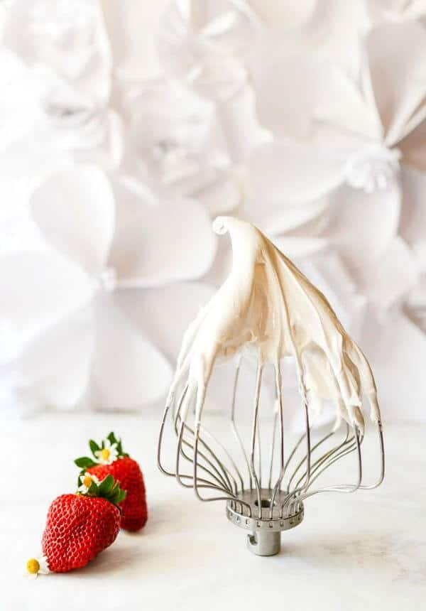 Two strawberries are placed near a balloon whisk covered in white meringue for the Pavlova recipe