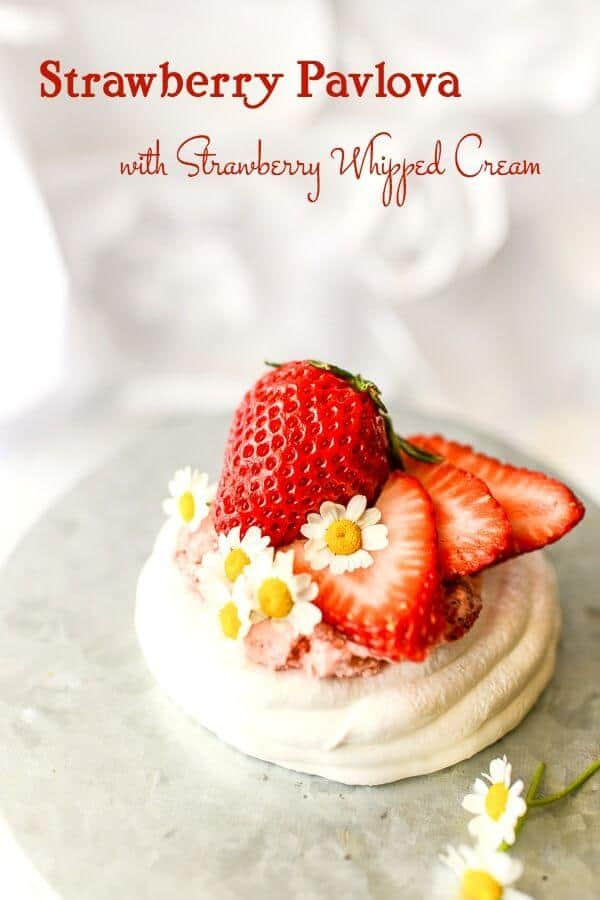 A small, white pavlova recipe with strawberry whipped cream and ripe strawberries on top. White background.