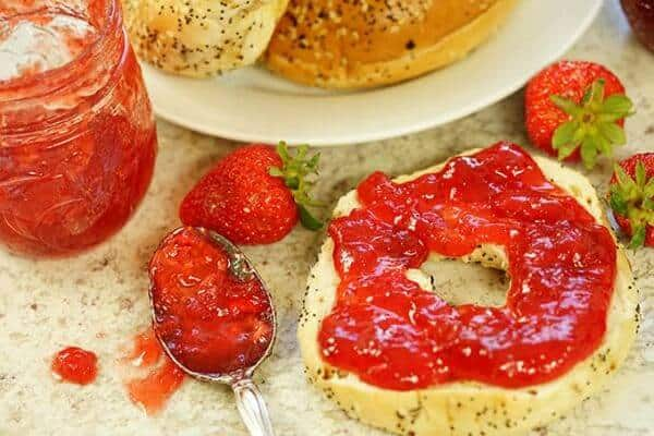 Strawberry jam has been spooned onto a bagel - optimized feature image.