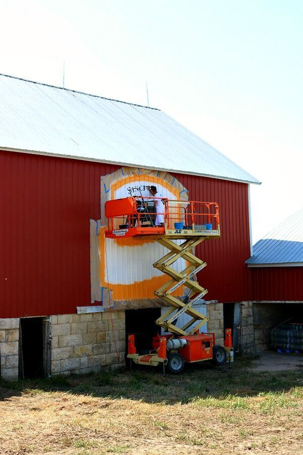 Artist painting the Certified Angus Beef ® Brand Logo on the Lyons-Blythe family farm.