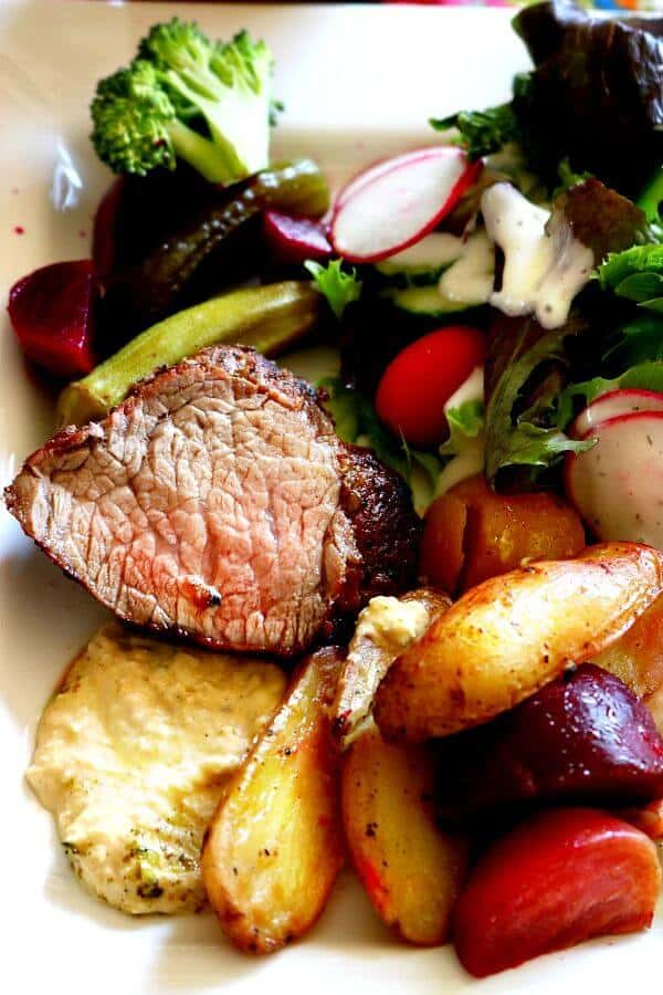 A plate with sliced angus beef, potatoes, beets, and salad on it