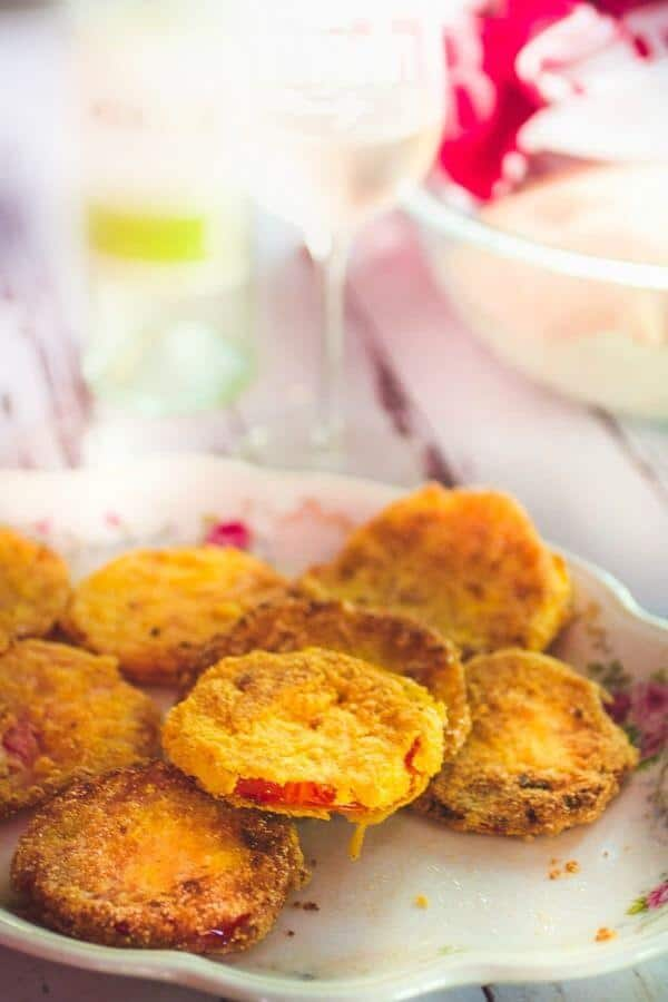 Crispy fried green tomatoes piled on a plate on a picnic table.