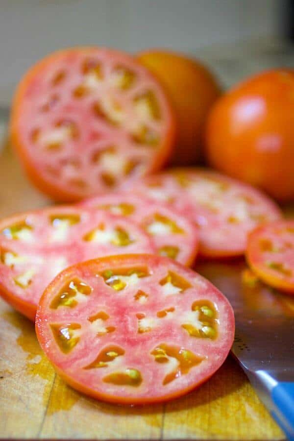 Sliced, partially ripened tomatoes for fried green tomatoes recipe.