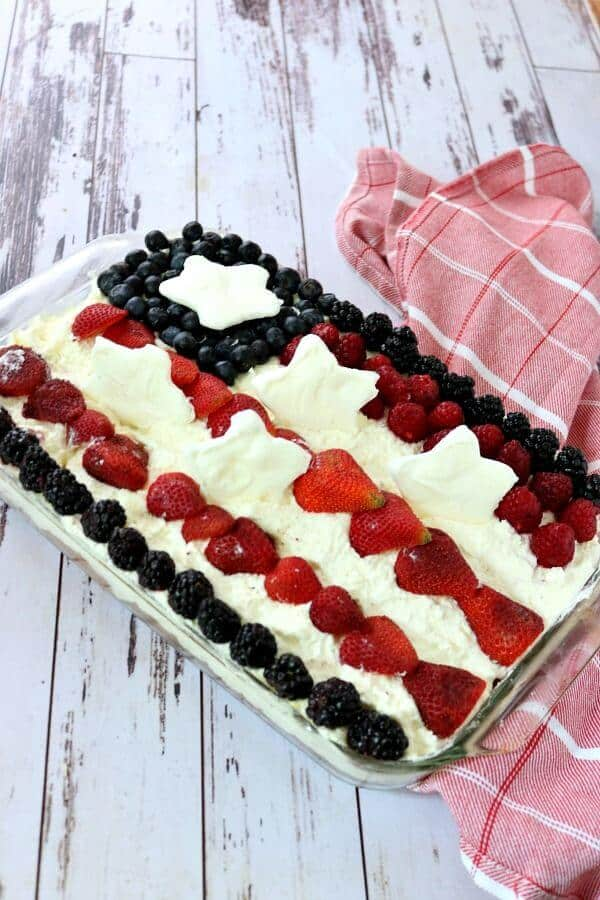 Square of Jello Poke cake with blueberries and raspberries on top.
