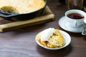 A dish of peach cobbler with whipped cream on top and a coffee cup to the side.