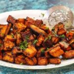 An antique platter of golden roasted sweet potatoes with a silver serving spoon