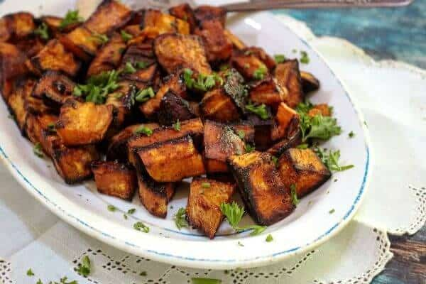 Closeup of cubed oven roasted sweet potatoes on a serving dish