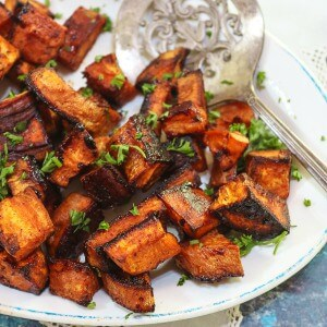 Oven roasted sweet potatoes cubed and roasted with chipotle and cinnamon. Recipe image