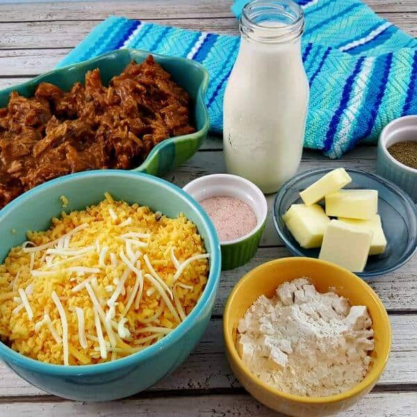 Ingredients to make Pulled Pork Mac and Cheese sit on a table with a turquoise kitchen towel. Ingredients include cheese in a light blue bowl, an oval dish of pulled pork, butter, cream, salt and pepper.