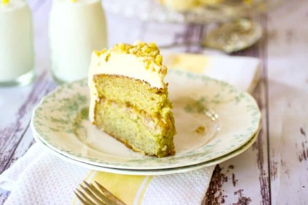banana layer cake with walnut filling on a plate with milk in the background