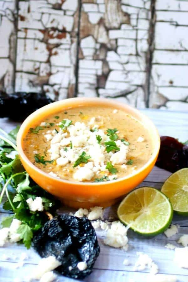 An orange bowl of Mexican Street Corn soup with limes at the base