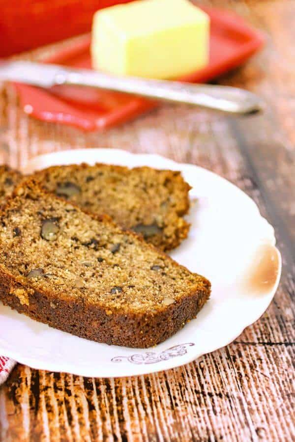 Slices of banana bread with a red butter dish in the background