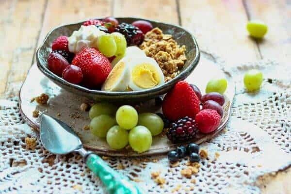 Granola, berries, eggs, and yogurt arranged in a bowl - feature image