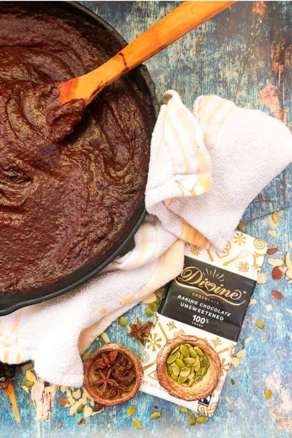 Mole sauce in an iron skillet with ingredients nearby