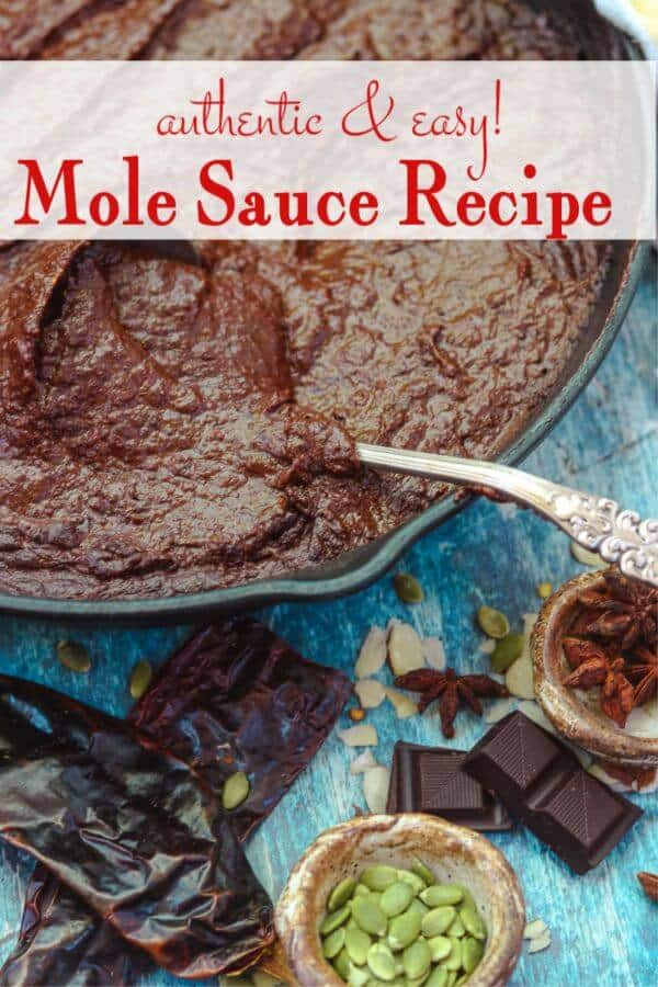 iron skillet filled with mole poblano sauce with a silver ladle