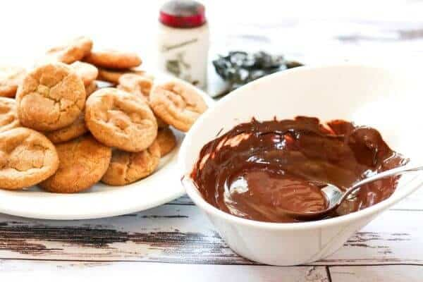 Melted chocolate in a white bowl with cookies in the background.