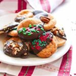 Decorated cinnamon crinkle cookies dipped in Mexican chocolate on a white plate.