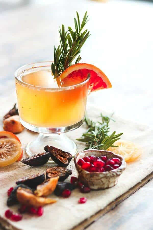 Old fashioned cocktail with an orange garnish and cut figs at the base of the glass.