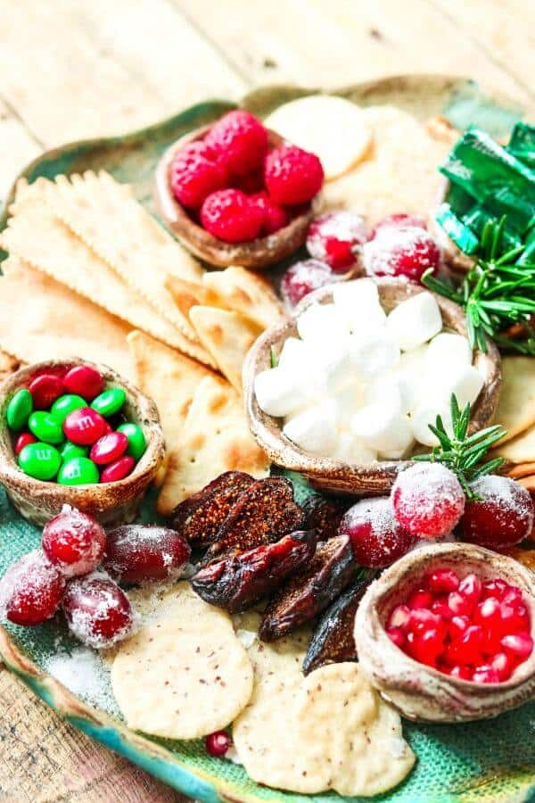 Figs, raspberries, grapes, and candy on a Christmas dessert tray.