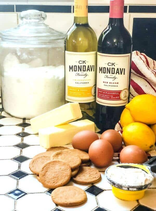 Lemons, cookies, and other ingredients for lemon bars on a tile countertop.