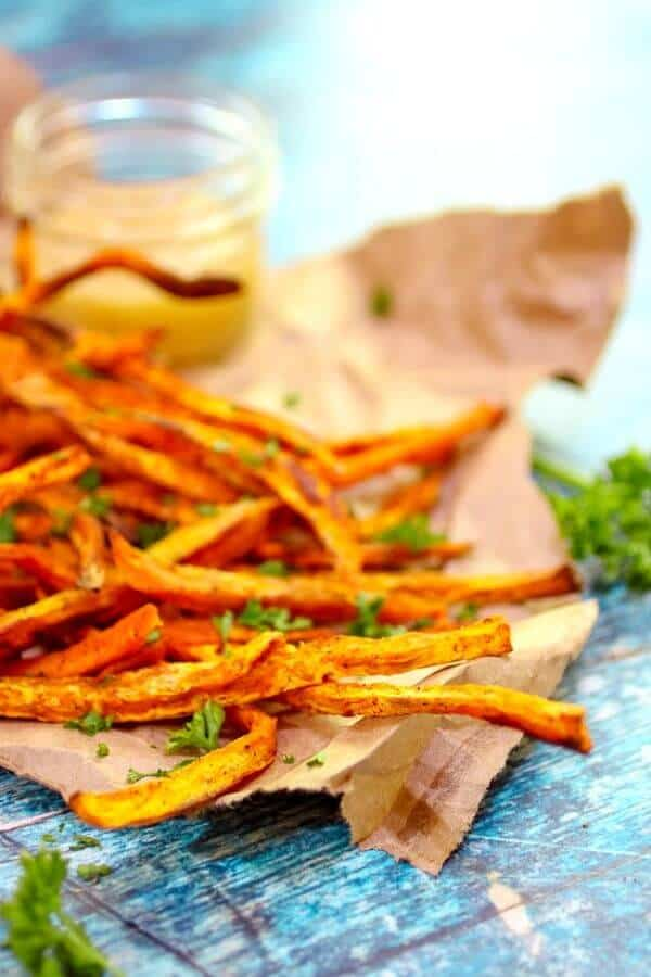 Crispy, homemade sweet potato fries with sauce in the background...close up to show texture.