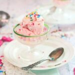 Pink ice cream in a vintage glass ice cream dish.