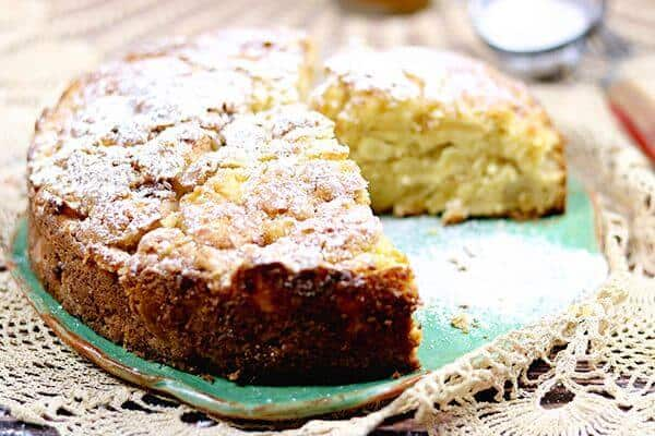 Delicious Irish Apple Cake with one slice removed on a green plate
