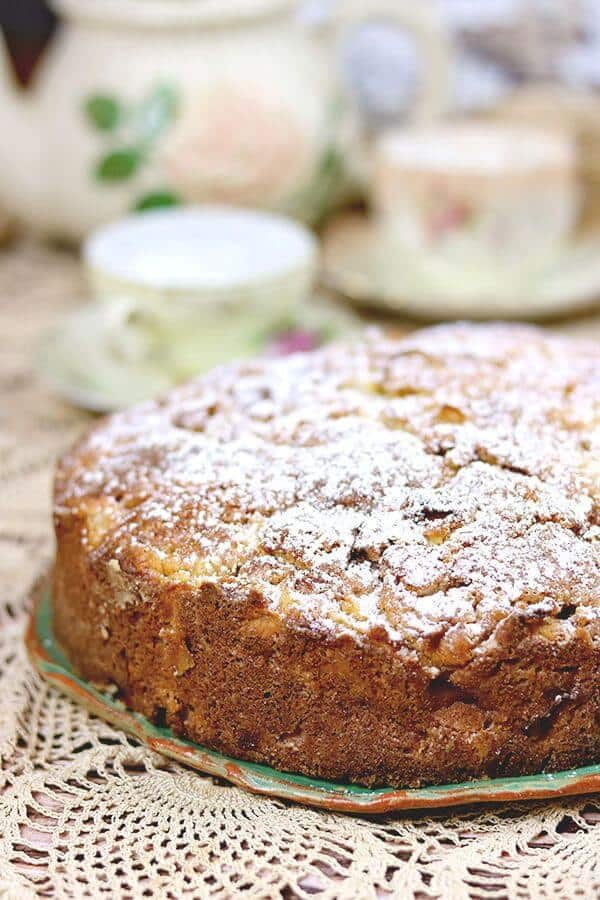 Authentic Irish Apple Cake, uncut, on a green plate placed on a lace tablecloth. Teapot and tea cups are in the background.