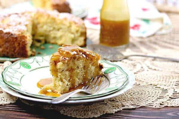 A slice of Irish Apple Cake with Whiskey Brown Butter Sauce on a vintage white and green plate