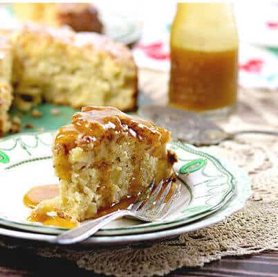 A thick slice of Irish Apple Cake is covered in brown butter whiskey sauce. The whole cake and the sauce in a bottle are in the background.