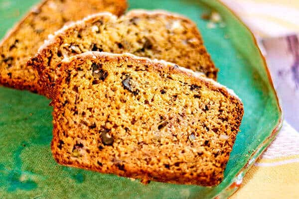 Close up of banana walnut bread slices on a dark green pottery plate.