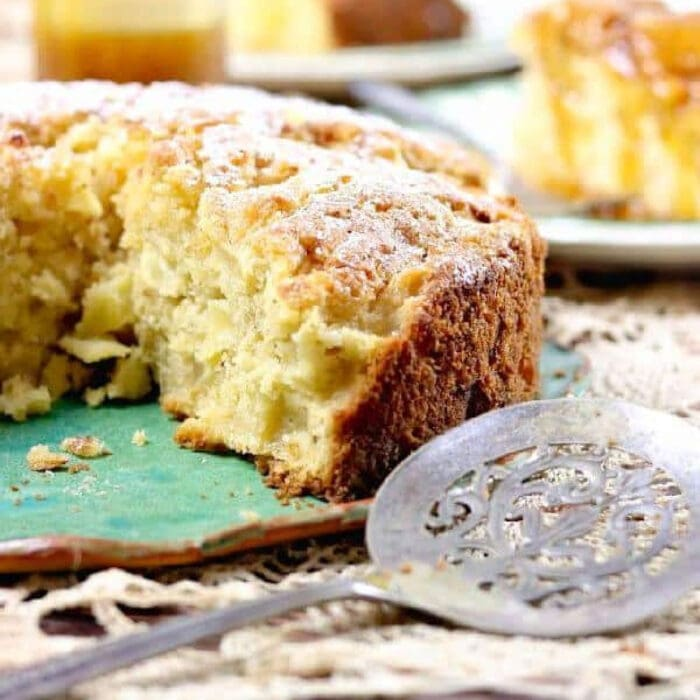 An apple cake with a slice taking out of it.