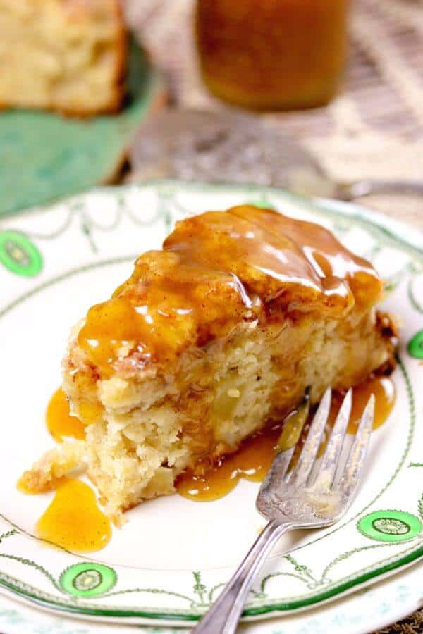 Closeup of a slice of Irish Apple Cake covered in whiskey brown butter sauce.