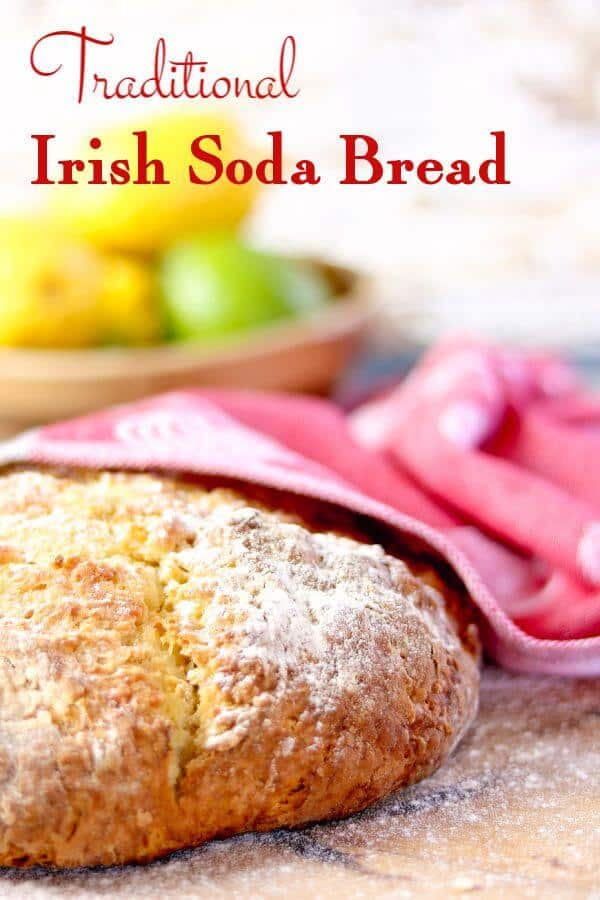 Round loaf of Irish soda bread cools under a red tea towel