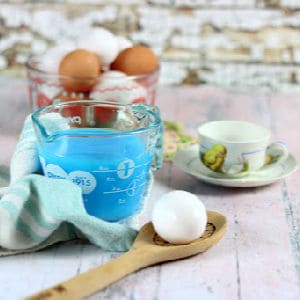 A cup of blue Kool Aid with an egg next to it.
