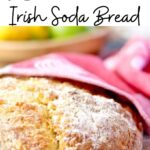 Round loaf of soda bread on a table. Text title overlay for Pinterest.