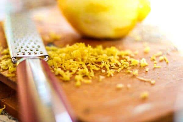 Lemon zest on a board with the microplane lying nearby