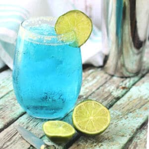 A glass of blue cocktail surrounded by slices of lime