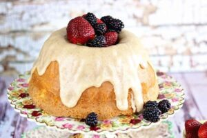A whole buttermilk pound cake on a plate with strawberries and blackberries.