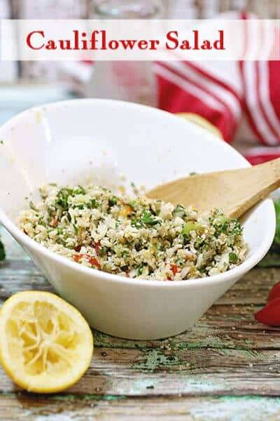 Title image - cauliflower salad in a white dish with a wooden spoon in it.