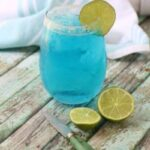 A glass filled with light blue lemonade and garnished with limes.