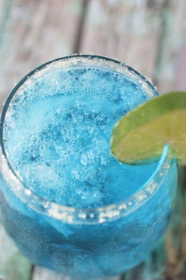 Top view of a glass of blue cocktail with ice.